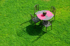 Iron garden table and chairs. On green grass Stock Photography