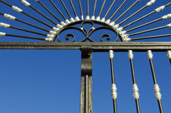 Iron gate. Detail of a beautiful iron gate against the blue clear sky Stock Image