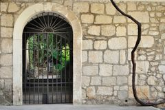 Iron gate in ancient stone wall Royalty Free Stock Images