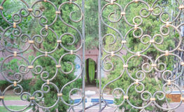 Iron gate. Beautiful retro and classical design of wrought iron brass gate and fence pattern with locked key, garden background Royalty Free Stock Photos