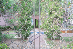 Iron gate. Beautiful retro and classical design of wrought iron brass gate and fence pattern with locked key, garden background Stock Images
