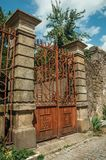 Iron gate covered by rust in front of old mansion. Vintage wrought iron gate covered by rust, in front of old mansion facade with stone decoration at Covilha royalty free stock photos