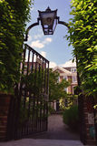 Iron gate door with the lantern leading to the private garden and house Royalty Free Stock Photography