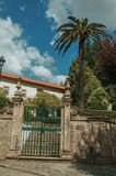 Iron gate in front of old building and green trees. Stone wall with iron gate in front of old building and green trees from a garden, in a sunny day at Gouveia royalty free stock image