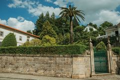 Iron gate in front of old building and green trees. Stone wall with iron gate in front of old building and green trees from a garden, in a sunny day at Gouveia stock photos