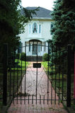Iron Gate House Entrance. Formal elite home with iron gate entrance before path stock photo