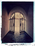 Iron gate leading to light,Polaroid image transfer. Corridor and iron gate in old building leading to light, Polaroid image transfer on watercolor paper, rough Stock Photos