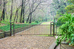 The iron gate and the path way to park Stock Photography