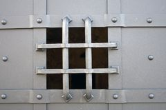 Iron gate small viewing hole. Small protected square viewing hole on a grey iron gate royalty free stock images