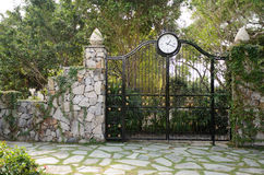 Iron gate in stone wall. In the park royalty free stock photos