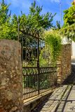 Iron gate to the garden in a wall stock photo