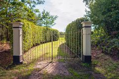 Iron gate between two stone pillars. Closed white painted iron gate between two white plastered stone pillars. Behind the gate is a sunny grass path between two royalty free stock photo