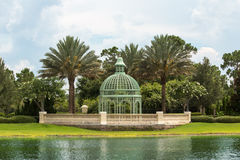 Iron Gazebo and Palm Trees. Green Dome Shaped Gazebo Constructed of Straight and Curved Iron Bars Sits Between Two Palm Trees and Other Green Vegitation Beside a Stock Images