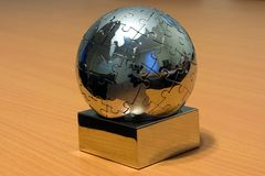 Iron globe puzzle. On the desk Stock Images