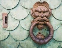 Iron goblin face doorknocker. On green wooden door Stock Images