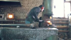 Iron hammer in front of craftsman blacksmith working with a hot steel. Blurred stock video footage