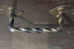 Iron hammered handle attached to a wooden surface Stock Photo