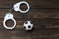 Iron handcuffs for the detention of criminals, a soccer ball on a wooden background. Arrest of fans, football fans royalty free stock photos