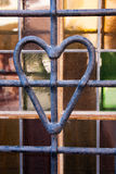 Iron heart in front of stain glass Stock Images
