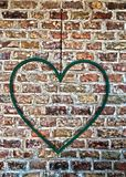Iron heart hanging on a brick wall royalty free stock photography