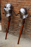 Iron helmets rest on crossbow. 3 iron helmets resting on 2 crossbows in the Palio di Siena in Italy Stock Photo