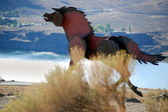 Iron Horse. Metal horse trotting on a ridge above a valley Royalty Free Stock Images