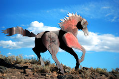 Iron horse. Metal horse up on a rocky ride with vibrant blue sky in the background Royalty Free Stock Photography