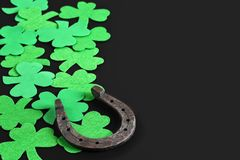 Iron horseshoe and clover on a dark background royalty free stock photo
