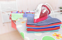 Iron and ironed clothes. Royalty Free Stock Photos