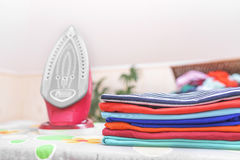 Iron and ironed clothes. Royalty Free Stock Photography