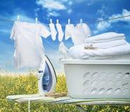 Iron on ironing board with basket Stock Image