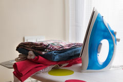 Iron on ironing board with clothes Stock Image