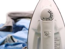 A iron and ironing board with clothes royalty free stock image