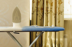 Iron on an ironing board Stock Photography