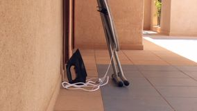 An iron and ironing board are located next to the hotel room stock video footage