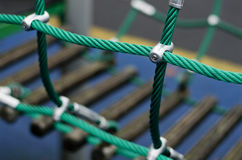 Iron joint point of ropes in children spider web with screw. Detail of cross green ropes in safety climbing outdoor equipment. Stock Photo