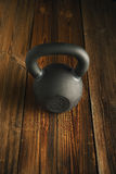 Iron kettlebell on wooden background Sport equipment background. Top view of black iron kettlebell on wooden background Sport equipment background with copyspace Stock Photography