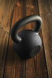 Iron kettlebell on wooden background Sport equipment background royalty free stock photos