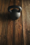 Iron kettlebell on wooden background Sport equipment background. Top view of black iron kettlebell on wooden background Sport equipment background with copyspace Stock Photo