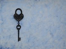 Iron key from the lock lying on wooden vintage background, top view Stock Photos