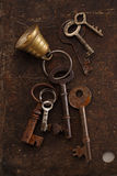 Iron keys with bell on metal backdrop Royalty Free Stock Photo