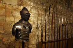 Iron knight. Armored Medieval knight with spears on the background in old castle Royalty Free Stock Photo