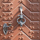 Iron knocker. Old iron knocker decorated with metal head and iron handle on wooden door Royalty Free Stock Image