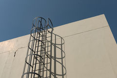 Iron ladder in cage to building roof top Royalty Free Stock Image