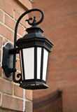 Iron Lamp. A iron made housing holds an outdoor lamp as its attached to a brick wall outside of a building Royalty Free Stock Image