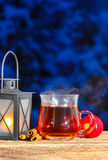 Iron lantern, steaming cup of tea and red apples Stock Photo