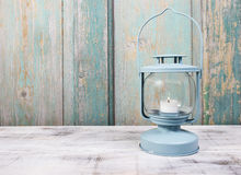 Iron lantern with white candle inside on wooden table Royalty Free Stock Images