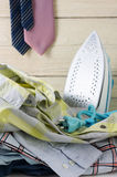 Iron and laundry housework. Laundry housework with pile of shirts and tie hanging Stock Images