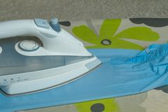 iron left on ironing board with blue shirt royalty free stock photos