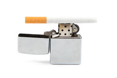 Iron lighter and cigarette on white Royalty Free Stock Images